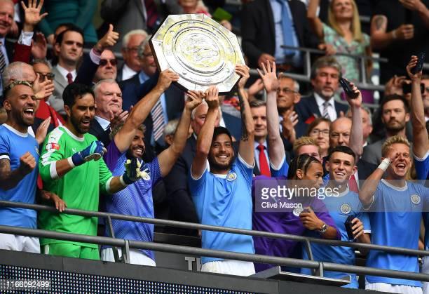 David Silva and Sergio Aguero of Manchester City lift the FA Community Shield following their team's victory in the FA Community Shield match at...