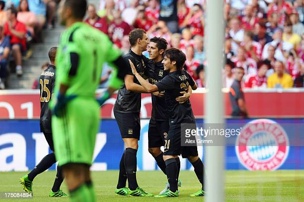 David Silva of Manchester celebrates his team's first goal with team mates Stefan Jovetic and Edin Dzeko during the Audi Cup match between Manchester...