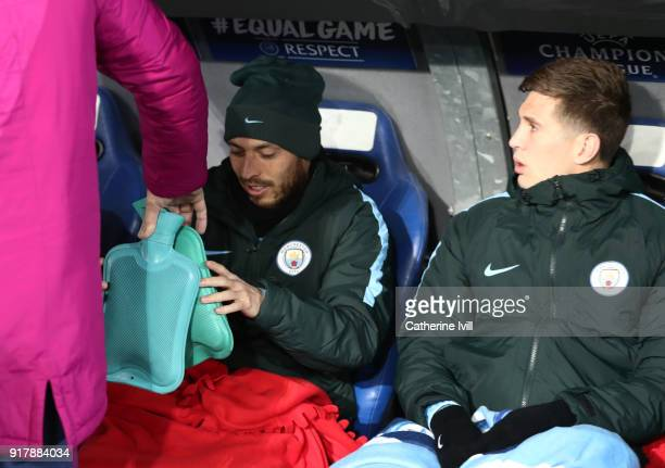 David Silva of Manchester City and John Stones of Manchester City is given a hot water bottle prior to the UEFA Champions League Round of 16 First...