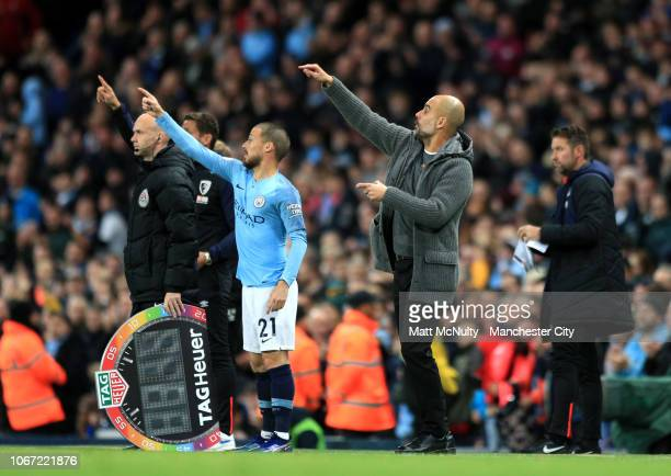 David Silva of Manchester City and Josep Guardiola Manager of Manchester City give their team instructions during the Premier League match between...
