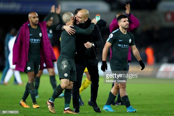 David Silva of Manchester City and Josep Guardiola Manager of Manchester City celebrate victory after the Premier League match between Swansea City...