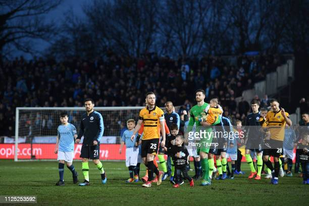 David Silva of Manchester City and Mark O'Brien of Newport County lead their teams out prior to the FA Cup Fifth Round match between Newport County...