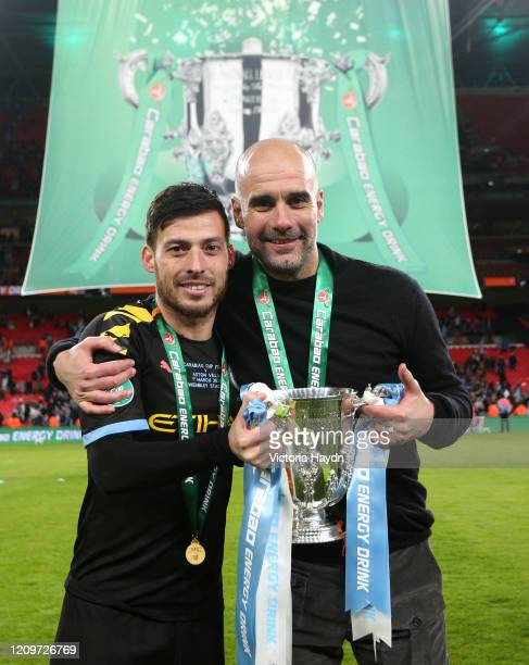 David Silva of Manchester City and Pep Guardiola, Manager of Manchester City pose with the trophy after the Carabao Cup Final between Aston Villa and...