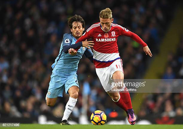David Silva of Manchester City and Viktor Fischer of Middlesbrough battle for possession during the Premier League match between Manchester City and...