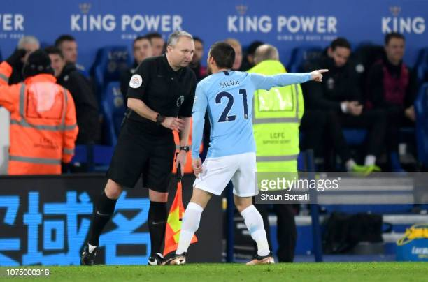 David Silva of Manchester City argues with the assistant referee Darren Cann during the Premier League match between Leicester City and Manchester...