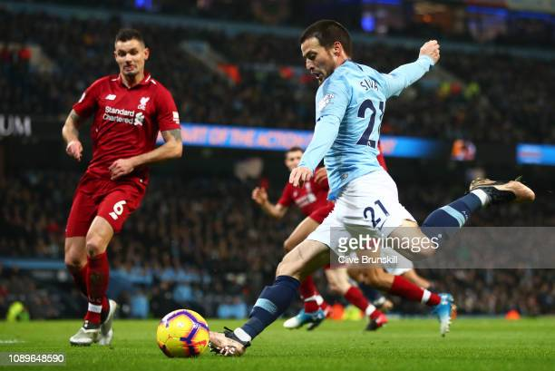 David Silva of Manchester City attempts to shoot past Dejan Lovren of Liverpool during the Premier League match between Manchester City and Liverpool...