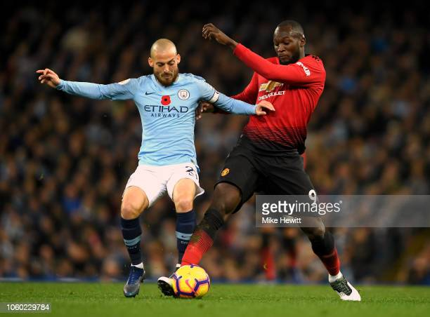 David Silva of Manchester City battles for possession with Romelu Lukaku of Manchester United during the Premier League match between Manchester City...