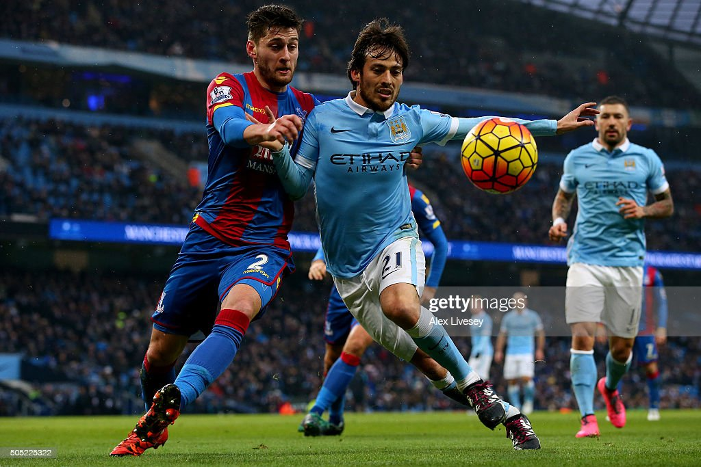 David Silva of Manchester City battles for the ball with Joel Ward of Crystal Palace during the Barclays Premier League match between Manchester City and Crystal Palace at Etihad Stadium on January 16, 2016 in Manchester, England.