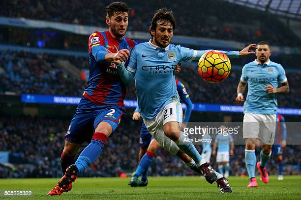 David Silva of Manchester City battles for the ball with Joel Ward of Crystal Palace during the Barclays Premier League match between Manchester City...
