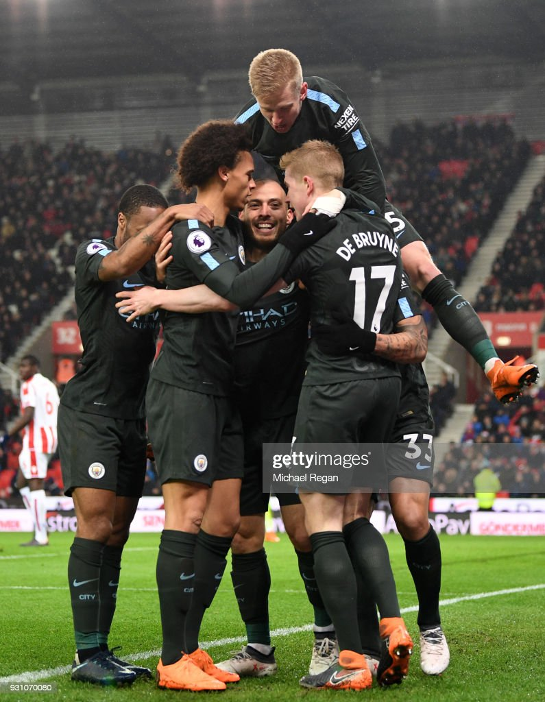 David Silva of Manchester City (C) celebrates as he scores their second goal with team mates during the Premier League match between Stoke City and Manchester City at Bet365 Stadium on March 12, 2018 in Stoke on Trent, England.
