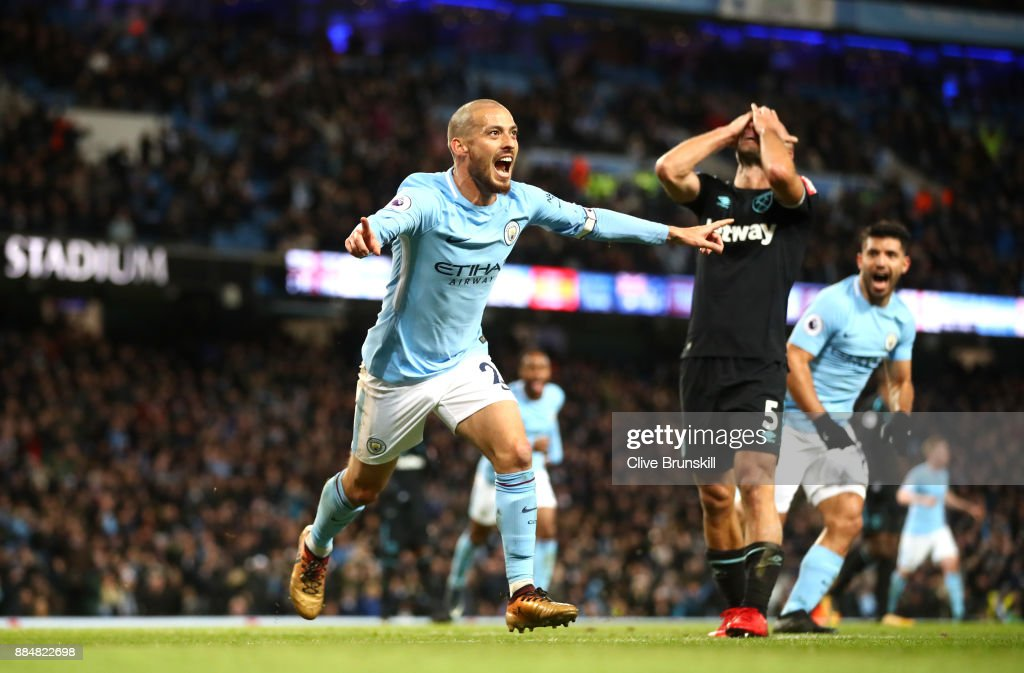 David Silva of Manchester City celebrates scoring his sides second goal while Pablo Zabaleta of West Ham United looks dejected during the Premier League match between Manchester City and West Ham United at Etihad Stadium on December 3, 2017 in Manchester, England.