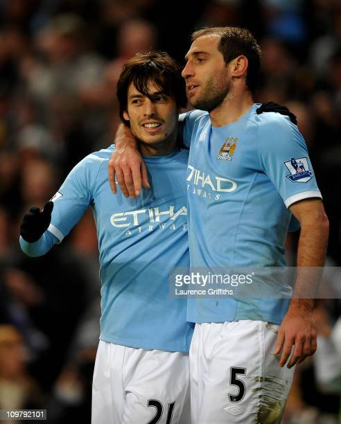 David Silva of Manchester City celebrates scoring the opening goal with team mate Pablo Zabaleta during the Barclays Premier League match between...