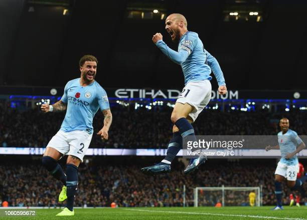 David Silva of Manchester City celebrates with teammate Kyle Walker after scoring his team's first goal during the Premier League match between...