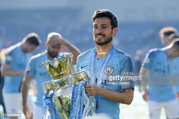 David Silva of Manchester City celebrates with the Premier League Trophy after winning the title following the Premier League match between Brighton...