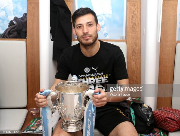 David Silva of Manchester City celebrates with the trophy in the changing room following his sides victory in the Carabao Cup Final between Aston...