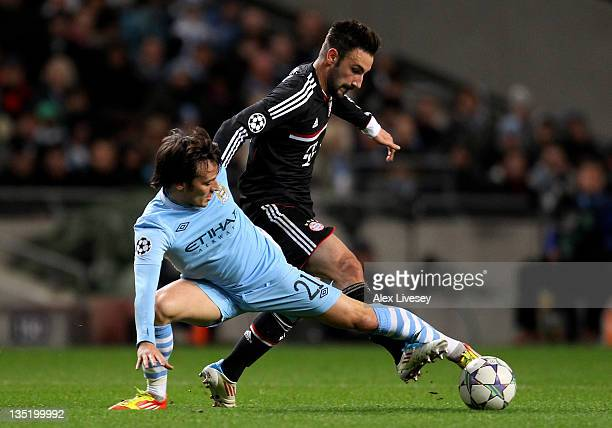 David Silva of Manchester City competes with Diego Contento of FC Bayern Muenchen during the UEFA Champions League Group A match between Manchester...