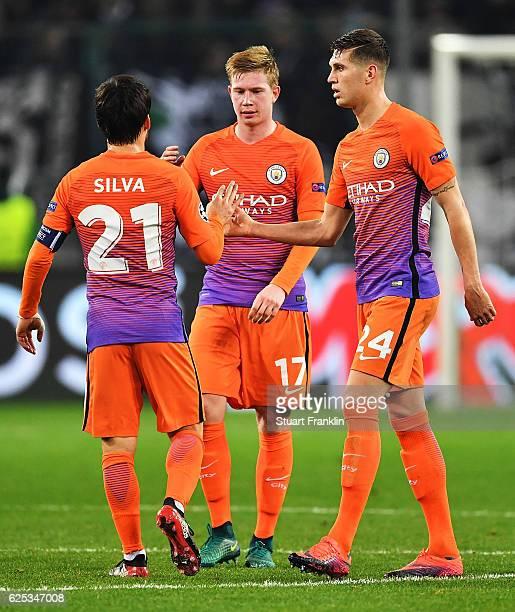 David Silva of Manchester City congratulates Kevin De Bruyne and John Stones after the UEFA Champions League match between VfL Borussia...