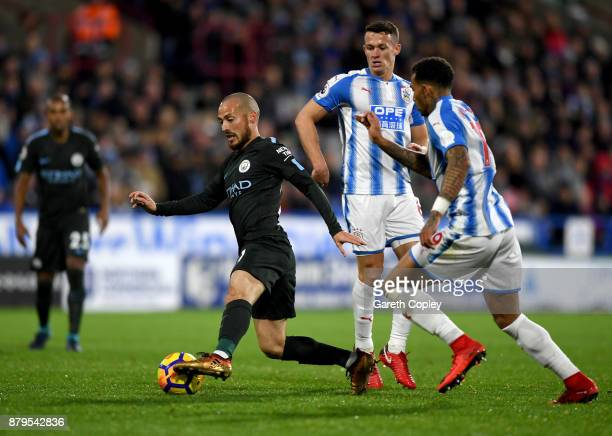 David Silva of Manchester City goes past Jonathan Hogg and Danny Williams of Huddersfield Town during the Premier League match between Huddersfield...