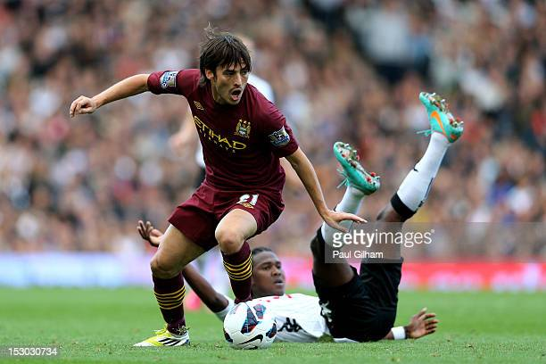David Silva of Manchester City goes past the challenge from Hugo Rodallega of Fulham during the Barclays Premier League match between Fulham and...