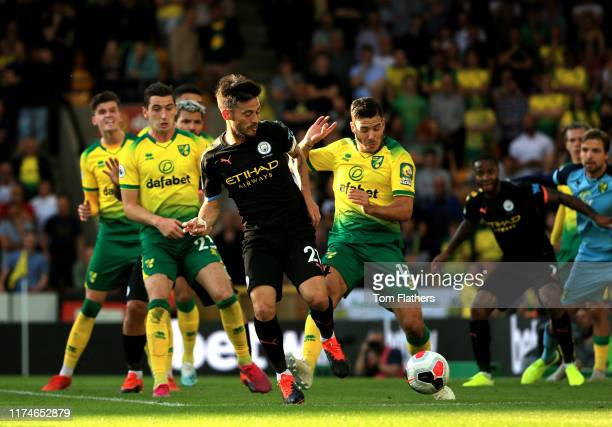David Silva of Manchester City is challenged by Emiliano Buendia of Norwich City during the Premier League match between Norwich City and Manchester...