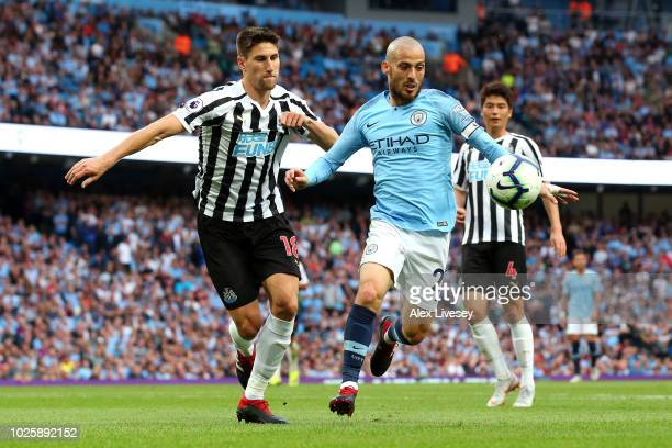 David Silva of Manchester City is challenged by Federico Fernandez of Newcastle United during the Premier League match between Manchester City and...