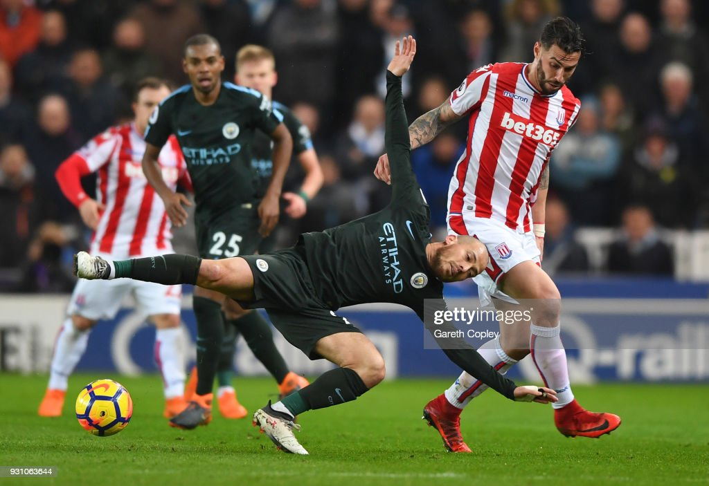 David Silva of Manchester City is challenged by Geoff Cameron of Stoke City during the Premier League match between Stoke City and Manchester City at Bet365 Stadium on March 12, 2018 in Stoke on Trent, England.