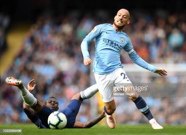 David Silva of Manchester City is challenged by Jean Michael Seri of Fulham during the Premier League match between Manchester City and Fulham FC at...