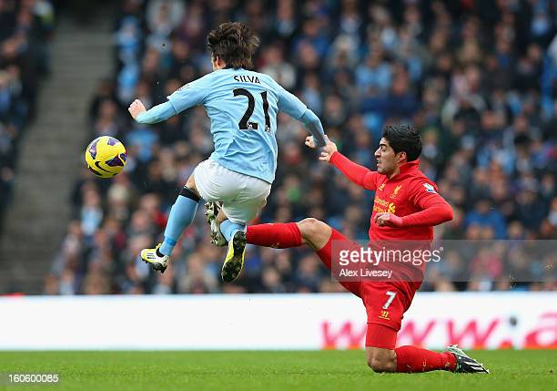 David Silva of Manchester City is challenged by Luis Suarez of Liverpool during the Barclays Premier League match between Manchester City and...