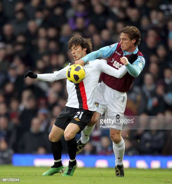 David Silva of Manchester City is challenged by Scott Parker of West Ham United during a Barclays Premier League match at Upton Park on December 11...