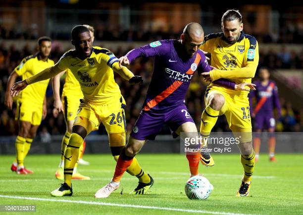 David Silva of Manchester City is challenged by Shandon Baptiste of Oxford United and Ricky Holmes of Oxford United during the Carabao Cup Third...
