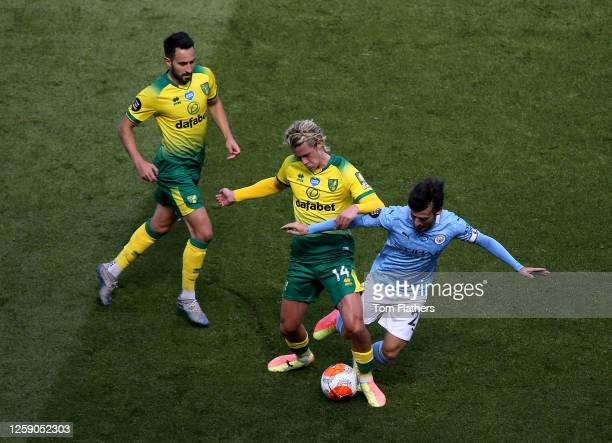David Silva of Manchester City is challenged by Todd Cantwell of Norwich City during the Premier League match between Manchester City and Norwich...