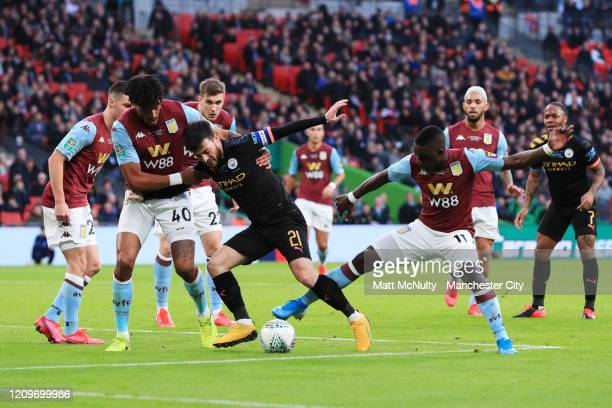 David Silva of Manchester City is challenged by Tyrone Mings and Marvelous Nakamba of Aston Villa during the Carabao Cup Final between Aston Villa...