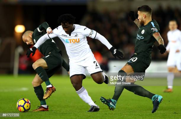 David Silva of Manchester City is challenged by Wilfried Bony of Swansea City during the Premier League match between Swansea City and Manchester...