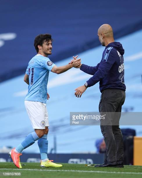 David Silva of Manchester City is greeted by Pep Guardiola Manager of Manchester City after being substituted on his final performance for Manchester...