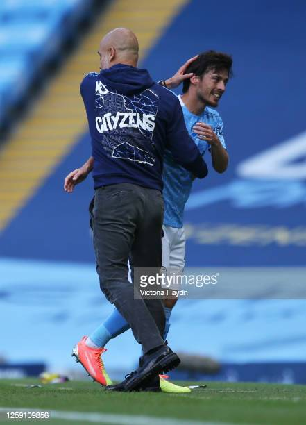 David Silva of Manchester City is greeted by Pep Guardiola, Manager of Manchester City after being substituted on his final performance for...