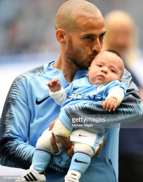 David Silva of Manchester City is seen with his son Mateo as the teams line up prior to the Premier League match between Manchester City and...
