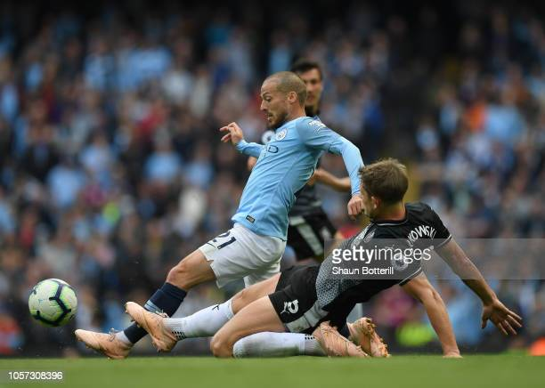 David Silva of Manchester City is tackled by James Tarkowski of Burnley during the Premier League match between Manchester City and Burnley FC at...