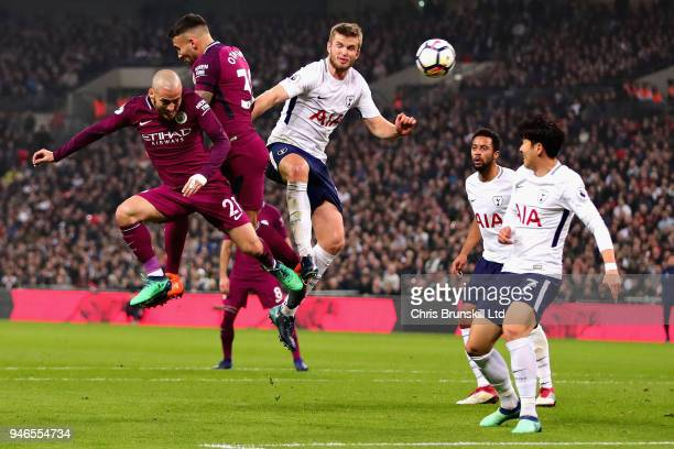 David Silva of Manchester City Nicolas Otamendi of Manchester City and Eric Dier of Tottenham Hotspur challenge for a header during the Premier...