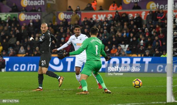 David Silva of Manchester City scores his sides first goal past Lukasz Fabianski of Swansea City during the Premier League match between Swansea City...
