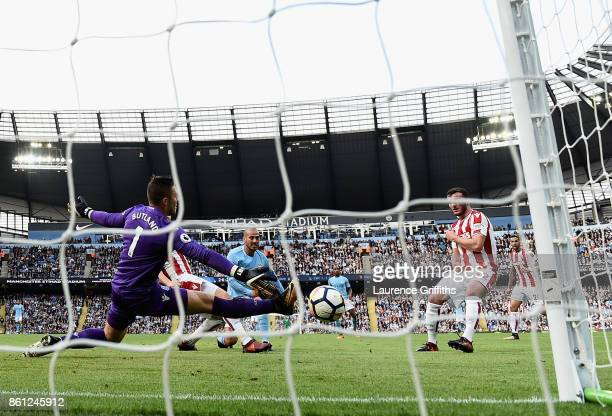 David Silva of Manchester City scores his sides third goal past Jack Butland of Stoke City during the Premier League match between Manchester City...