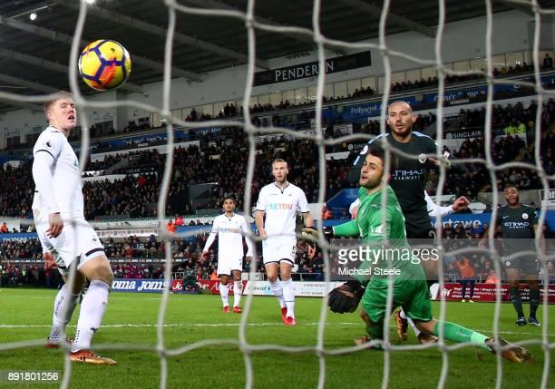 David Silva of Manchester City scores his sides third goal past Lukasz Fabianski of Swansea City during the Premier League match between Swansea City...