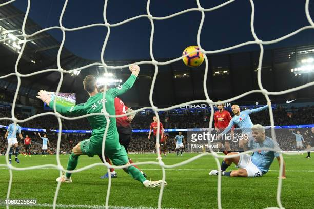 David Silva of Manchester City scores his team's first goal past David De Gea of Manchester United during the Premier League match between Manchester...