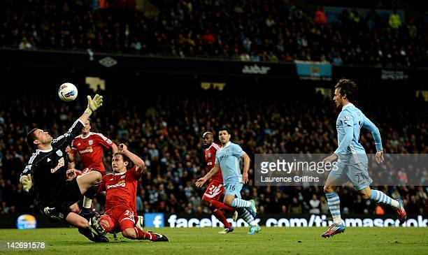David Silva of Manchester City scores his team's fourth goal during the Barclays Premier League match between Manchester City and West Bromwich...