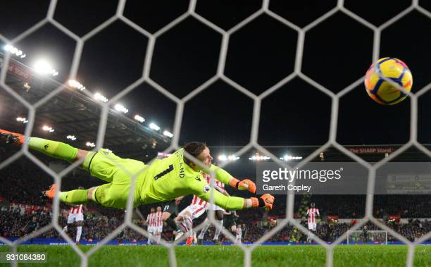 David Silva of Manchester City scores their first goal past Jack Butland of Stoke City during the Premier League match between Stoke City and...