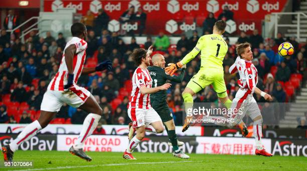 David Silva of Manchester City scores their second goal past Jack Butland of Stoke City during the Premier League match between Stoke City and...