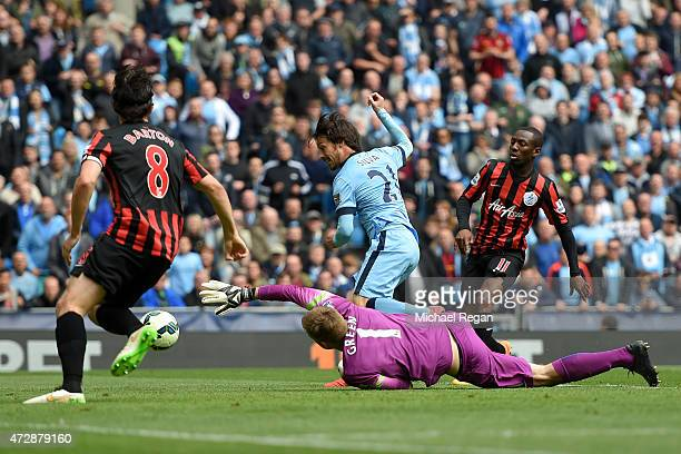 David Silva of Manchester City scres his team's sixth goal past the outstretched Robert Green of QPR during the Barclays Premier League match between...