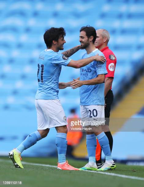 David Silva of Manchester City shakes hands with teammate Bernardo Silva as he is substituted on his final appearance for Manchester City during the...