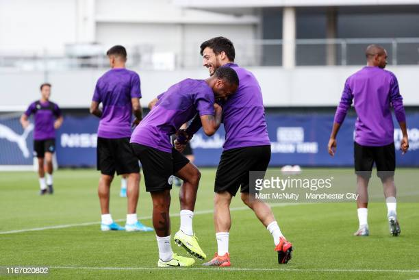 David Silva of Manchester City shares a joke with teammate Raheem Sterling during the training session at Manchester City Football Academy on August...