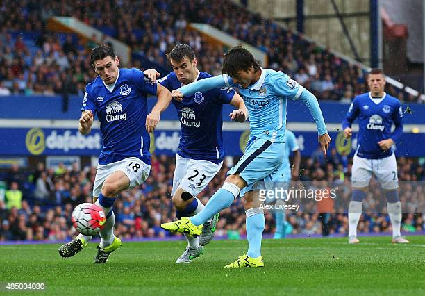 David Silva of Manchester City shoots as he is closed down by Gareth Barry and Seamus Coleman of Everton during the Barclays Premier League match...