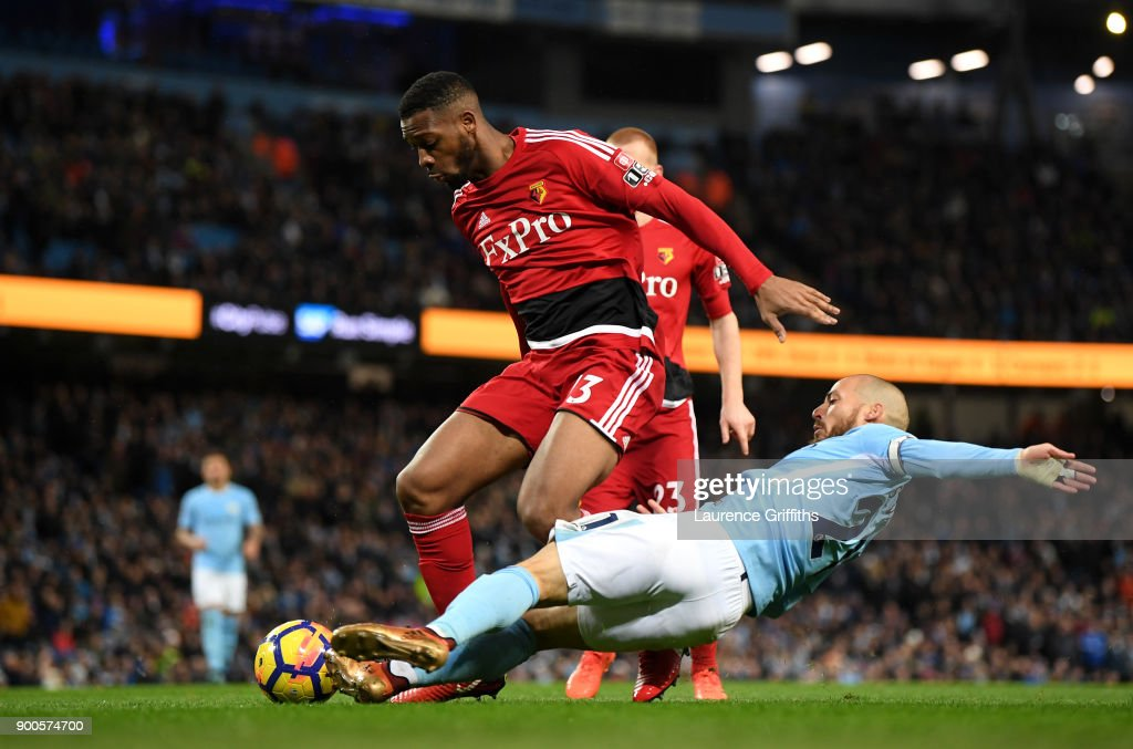 David Silva of Manchester City tackles Molla Wague of Watford during the Premier League match between Manchester City and Watford at Etihad Stadium on January 2, 2018 in Manchester, England.